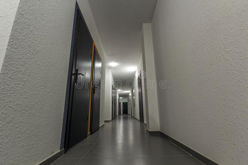 Narrow white corridor with many doors in an apartment building stock photo