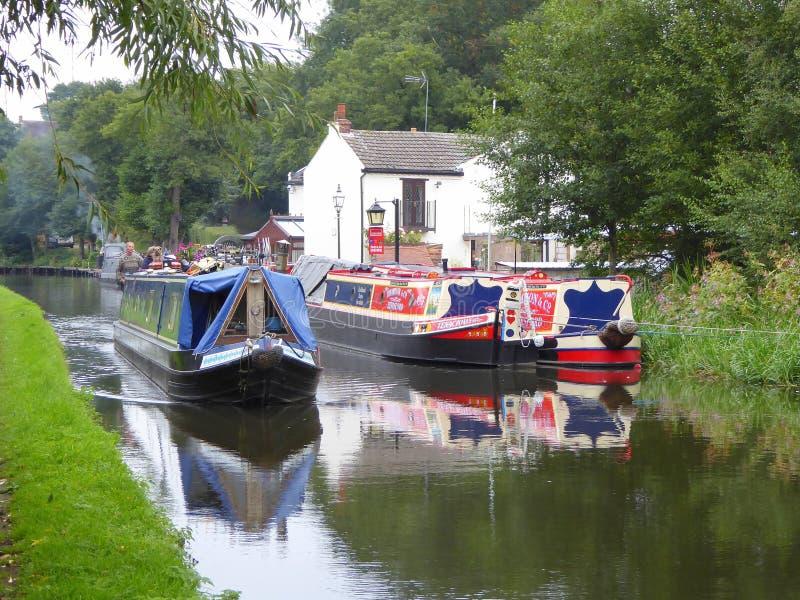 Narrowboat som kryssar omkring förbi stugaförtöjning royaltyfria foton