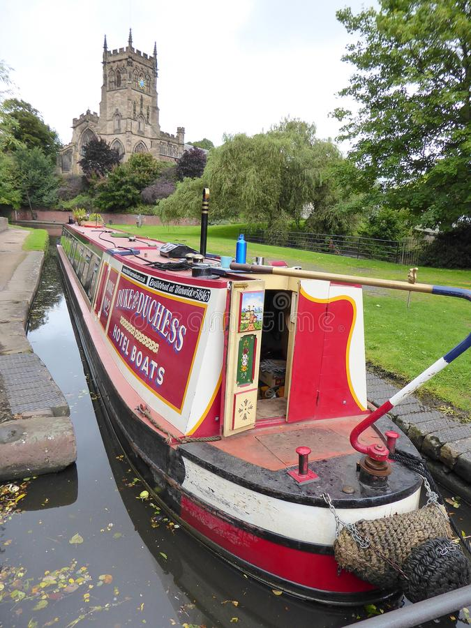 Narrowboat sur le canal par l'église images libres de droits