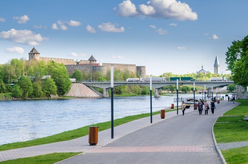 Narva flodinvallning med semesterfirarefolk och gränsen av Ryssland och den europeiska unionen royaltyfria bilder