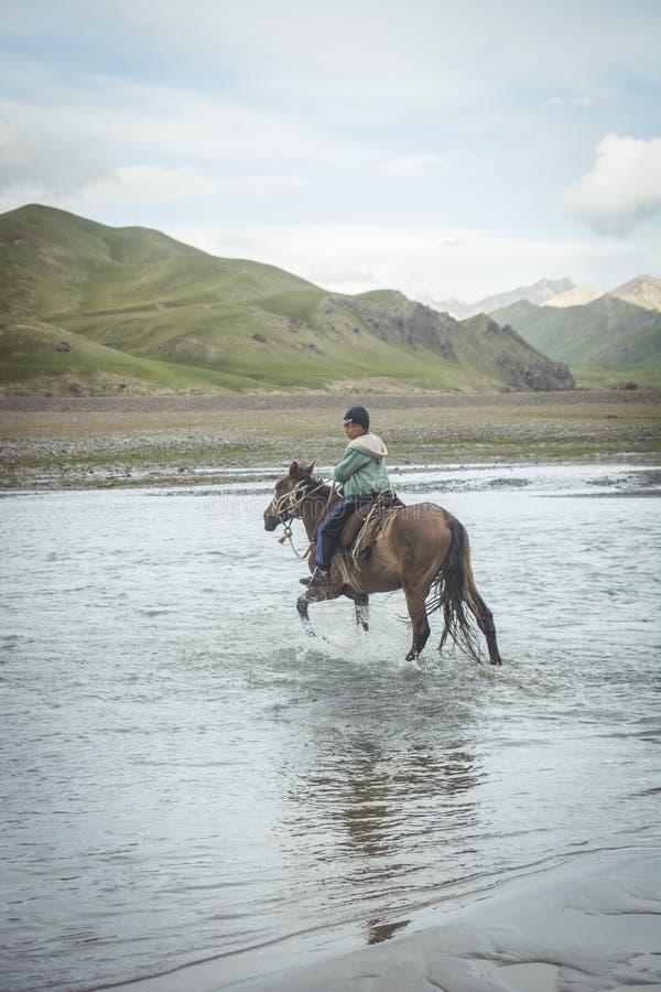 NARYN-PROVINZ, Kirgisistan - 21. Juli 2016: Junge, der sein Pferd am Abend, zur anderen Seite von einem starken Fluss nahe ihm re lizenzfreies stockfoto