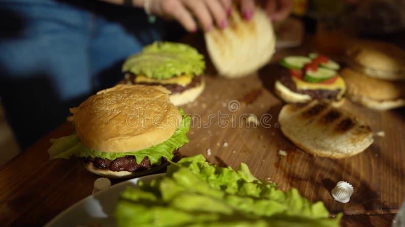 Narządzanie hamburgery, robi hamburgerowi, składnikom dla kulinarnych hamburgerów, warzywom, serowi i warzywom, na stole obrazy royalty free