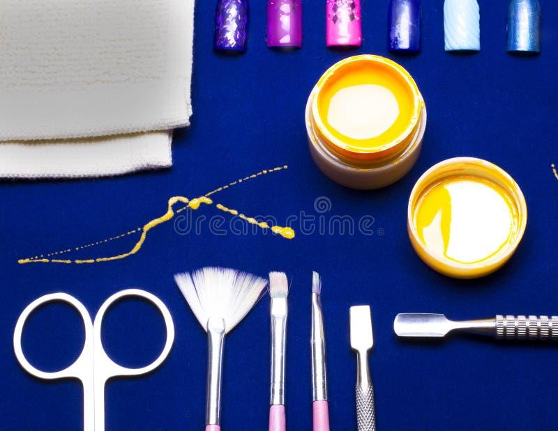 Narzędzia dla manicure'u, gel gwoździa koloru kolor żółty, upaćkany jata brygadier przy błękitnym stołem odporny zdjęcia stock