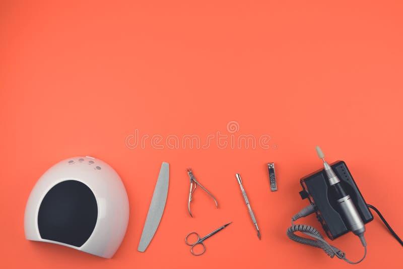 Narzędzia hybrydowy manicure, gwóźdź opieka ustawia na koralowym tle Elektryczna gwoździa świderu maszyna, DOWODZONA lampa, karto fotografia royalty free