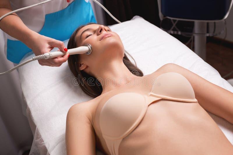 Narzędzia kosmetologia Zbliżenie obrazek szczęśliwa młoda kobieta z zamkniętymi oczami dostaje rf podnośną procedurę w pięknie zdjęcia stock