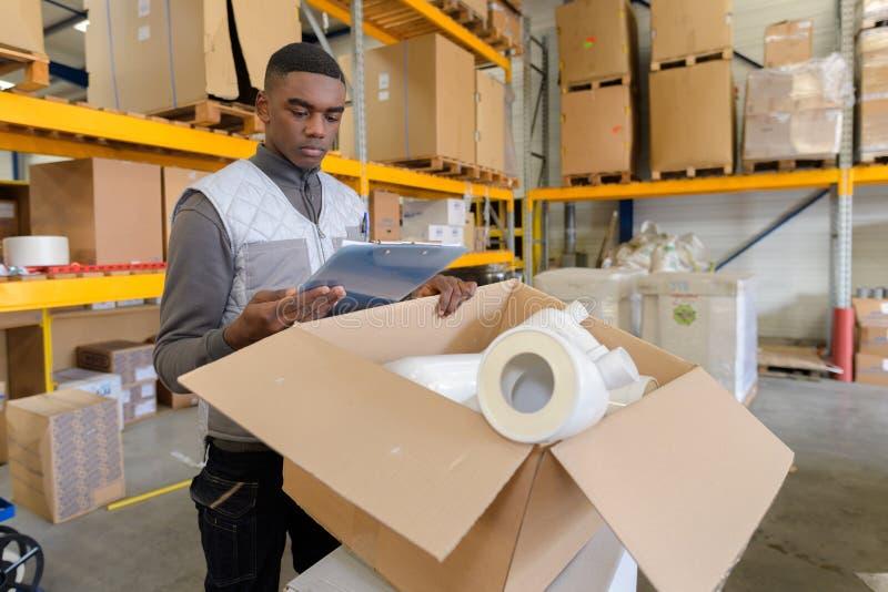 Narzędzia sklepu pracownik sprawdza dostawy w magazynie obraz stock