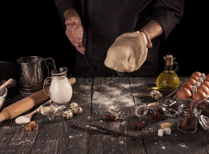 Narzędzie dla ciasta ugniatać, jedzenia i skończonego ciasta w rękach, odizolowywać na czerni zdjęcia stock
