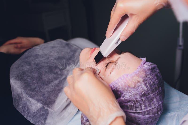 Narz?dzia kosmetologia Beautician robi chromotherapy ultrad?wi?kowi czy?ci klient twarz Sk?ry por czy?ci? anty obrazy stock