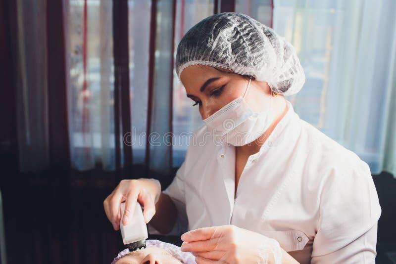 Narz?dzia kosmetologia Beautician robi chromotherapy ultrad?wi?kowi czy?ci klient twarz Sk?ry por czy?ci? anty zdjęcia stock