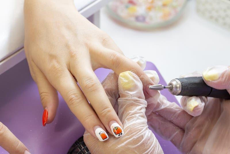 Narz?dzia manicure manicurzysta robi gwoździowi półkowemu froterowaniu klient z manicure'u przyrządem fotografia stock