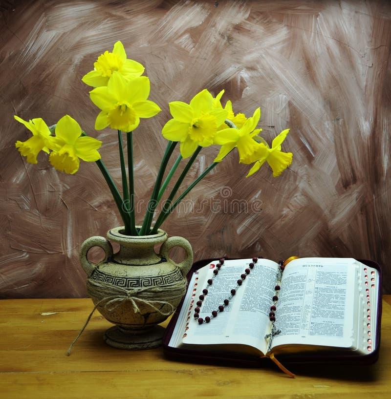 Narzissen in einer Lehmwanze auf einem Holztisch, offene Bibel stockfoto