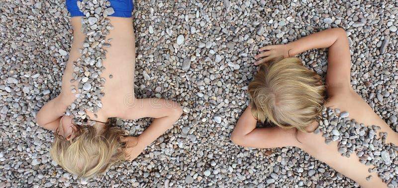 Nas crianças ensolaradas da praia que encontram-se no seixo, aquecendo-se após nadar imagens de stock