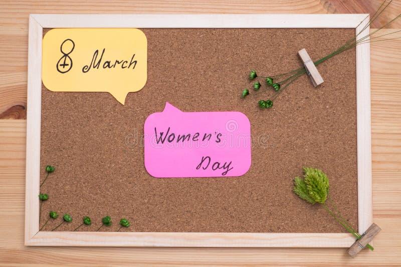 Nas etiquetas da placa da cortiça com o dia inscrição das mulheres do 8 de março imagem de stock