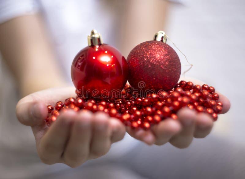 Nas mãos de bolas e de grânulos do Natal das crianças Natal, ano novo imagens de stock royalty free
