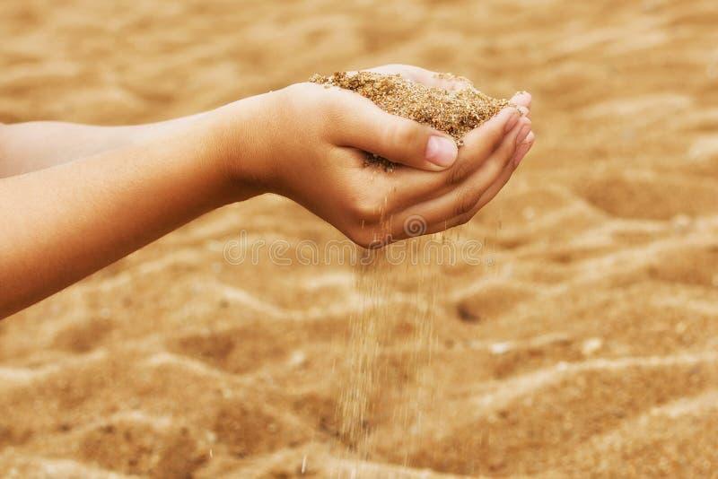 Nas palmas abertas lixe que derrama através dos dedos Mulher nova com a areia nas mãos imagens de stock royalty free