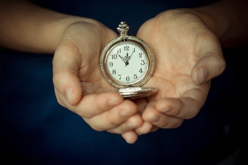 Nas palmas das crianças o pulso de disparo velho Fotografia conceptual O tempo é 11 55 Cinco minutos a doze imagem de stock