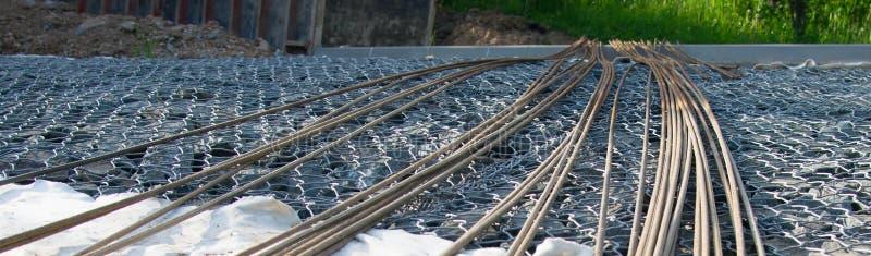 Nas pedras são as hastes de metal longas para o concreto, entrando na distância fotografia de stock