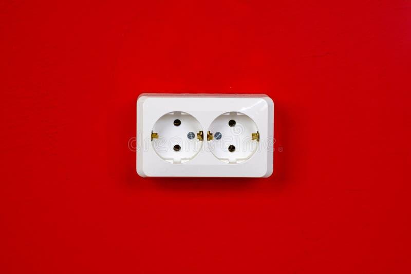 Nasadka na czerwonej ścianie kosmos kopii Poj?cie energia - savings Bia?a elektryczna nasadka na czerwonej ?cianie zbli?enie obrazy royalty free