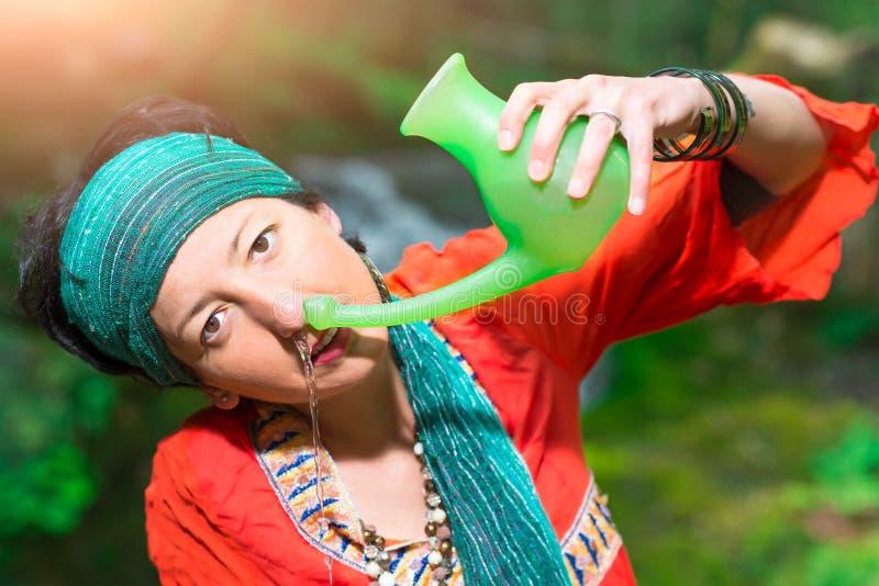 Nasal bevattning för Jala neti med en kvinna i natur arkivfoton