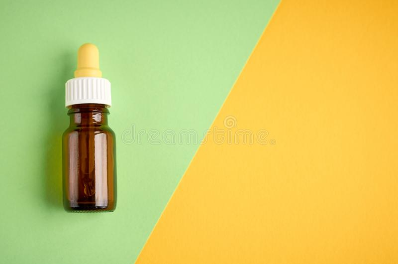 Nasal drops bottle composition, glass bottle on yellow and green background. Flat lay and top view photo nose medicine health medical care cold treatment royalty free stock photography