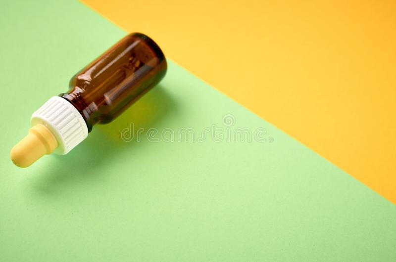 Nasal drops bottle composition, glass bottle on yellow and green background. Flat lay and top view photo nose medicine health medical care cold treatment stock images