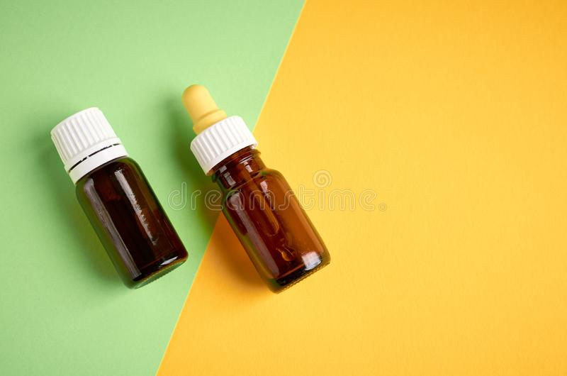 Nasal drops bottle composition, glass bottle on yellow and green background. Flat lay and top view photo nose medicine health medical care cold treatment royalty free stock photo