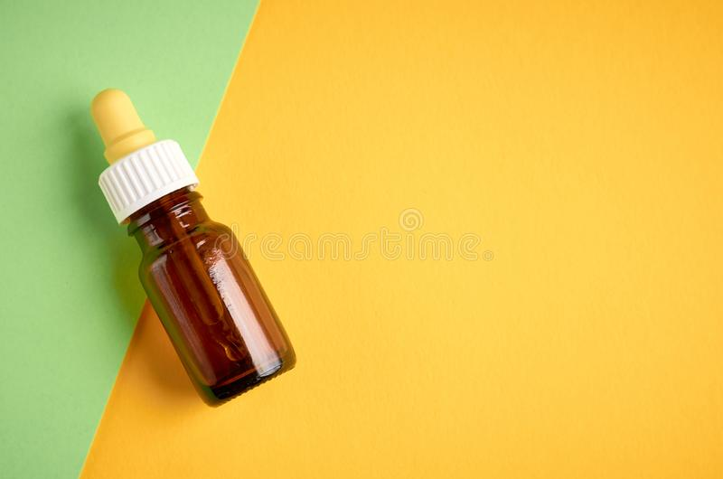 Nasal drops bottle composition, glass bottle on yellow and green background. Flat lay and top view photo, nose, medicine, health, medical, care, cold stock photos