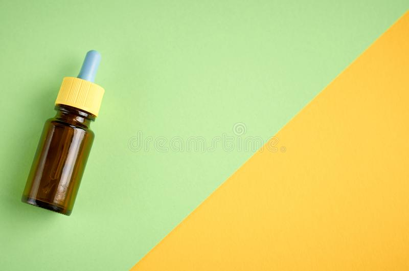 Nasal drops bottle composition, glass bottle on yellow and green background. Flat lay and top view photo, nose, medicine, health, medical, care, cold royalty free stock images