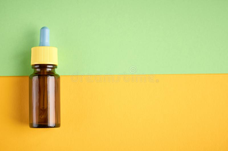 Nasal drops bottle composition, glass bottle on yellow and green background. Flat lay and top view photo nose medicine health medical care cold treatment stock photos