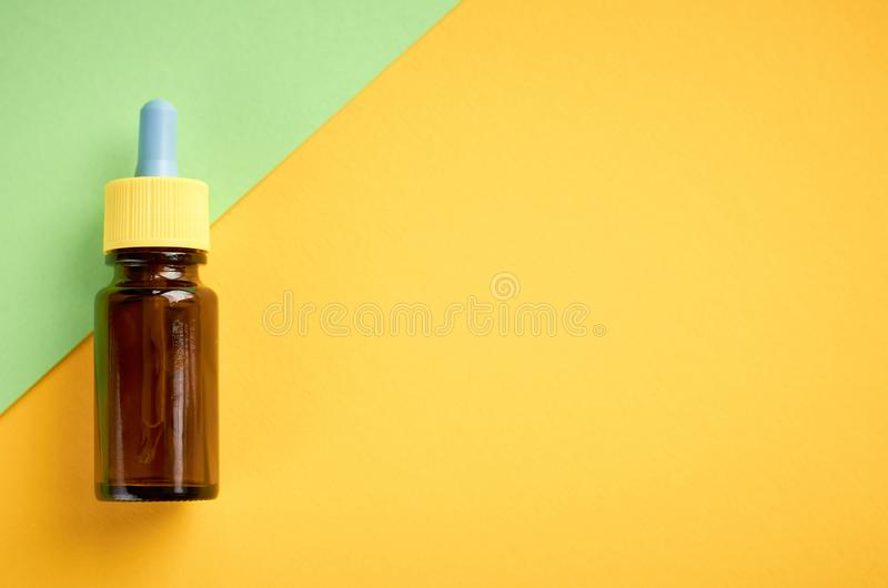 Nasal drops bottle composition, glass bottle on yellow and green background. Flat lay and top view photo nose medicine health medical care cold treatment stock photography