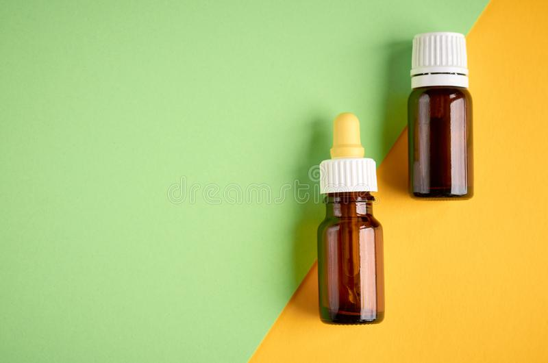 Nasal drops bottle composition, glass bottle on yellow and green background. Flat lay and top view photo, nose, medicine, health, medical, care, cold royalty free stock image