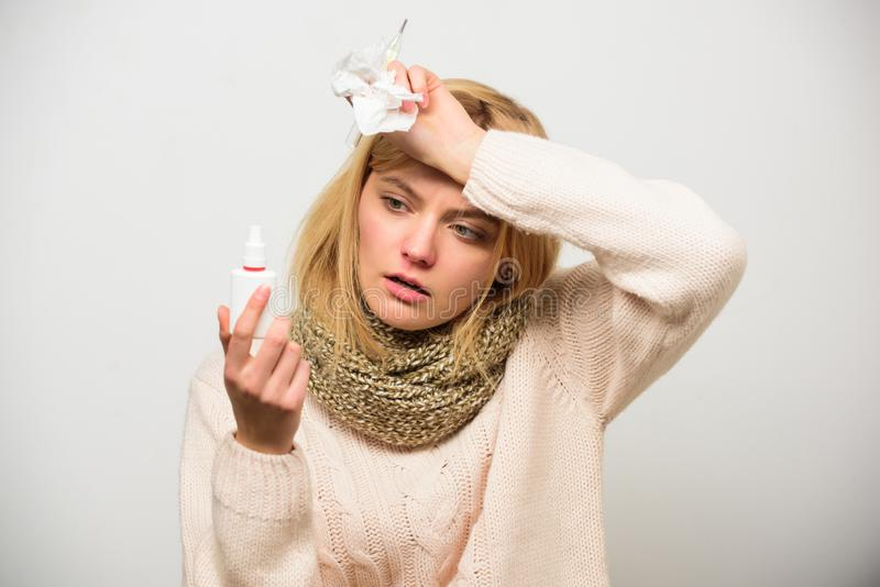 Nasal spray runny nose remedy. Woman feels badly ill sneezing. Girl in scarf hold nasal spray and tissue. Cold and flu. Remedies. Runny nose and other symptoms stock photos