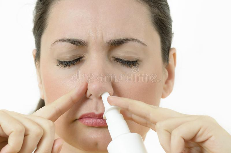 Nasal Spray. A young woman using nasal spray, covering nostril royalty free stock photo