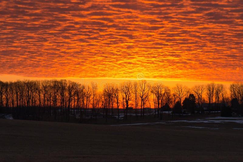 Nascer do sol alaranjado brilhante sobre o campo senic fotografia de stock