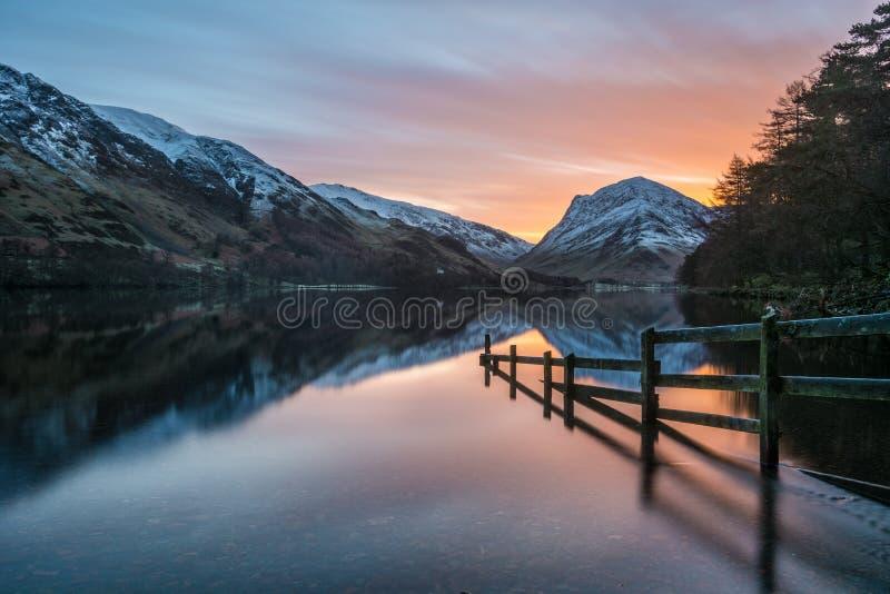 Nascer do sol alaranjado do inverno em Buttermere no distrito do lago, Reino Unido fotos de stock