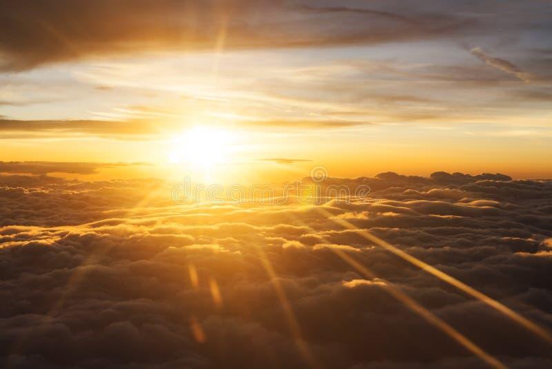 Nascer do sol alaranjado entre nuvens imagem de stock