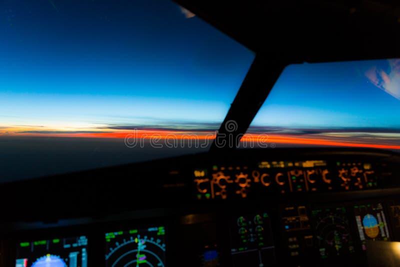 Nascer do sol do amanhecer - opinião dos capitães na plataforma de voo de um avião moderno do avião de passageiros imagens de stock royalty free