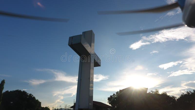 Nascer do sol atr?s da cruz tomada pelo zang?o imagem de stock