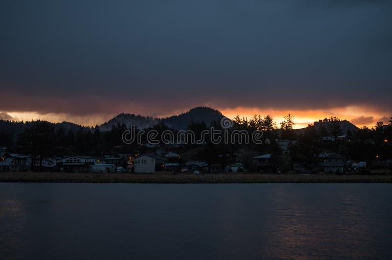 Nascer do sol atrás do monte na frente do rio na cidade litoral de Oregon foto de stock