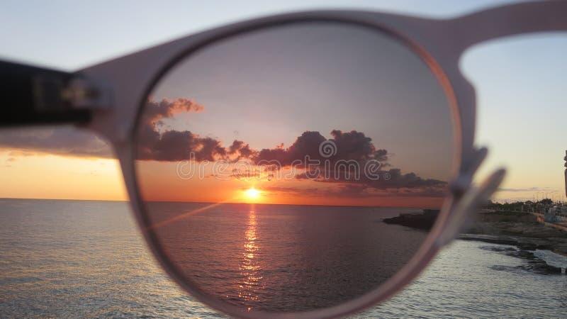 Nascer do sol através dos óculos de sol fotografia de stock royalty free