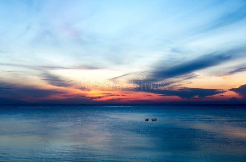 Nascer do sol bonito com o barco de pesca no mar imagens de stock royalty free