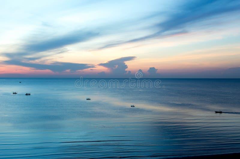 Nascer do sol bonito com o barco de pesca no mar fotos de stock royalty free