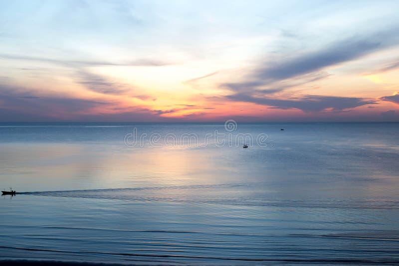 Nascer do sol bonito com o barco de pesca no mar imagem de stock