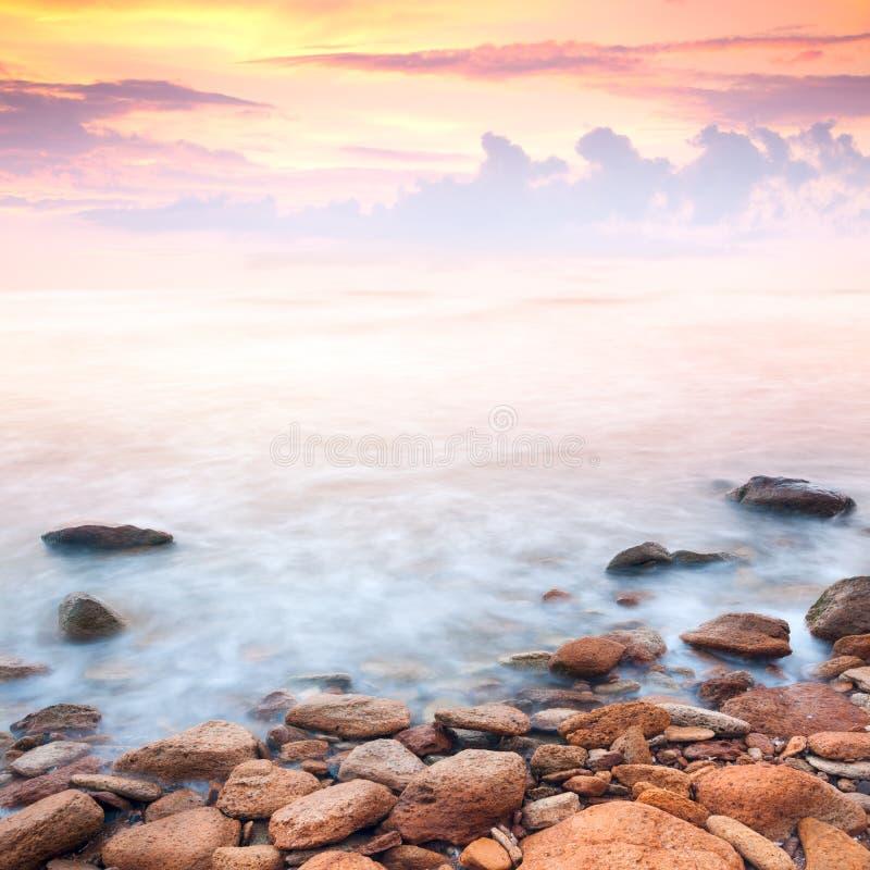 Nascer do sol bonito sobre a costa de mar rochosa imagem de stock royalty free