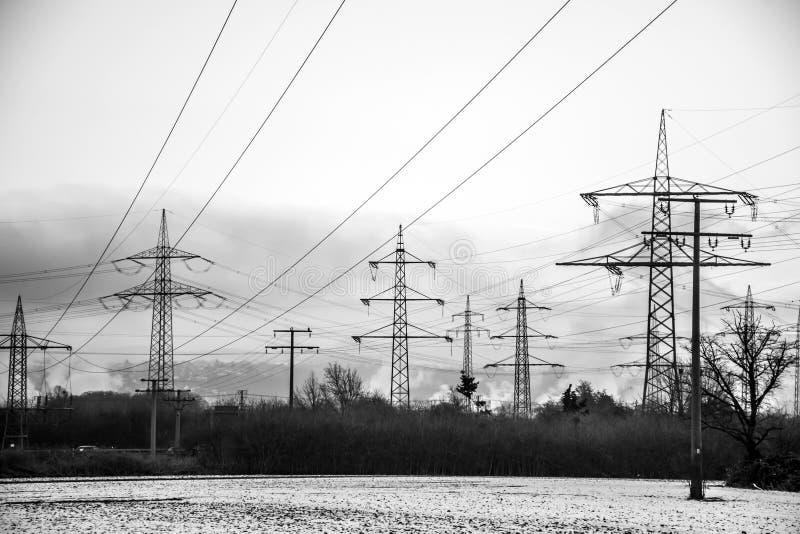 Nascer do sol branco do por do sol do preto da neve da paisagem da torre da energia elétrica do inverno imagem de stock royalty free