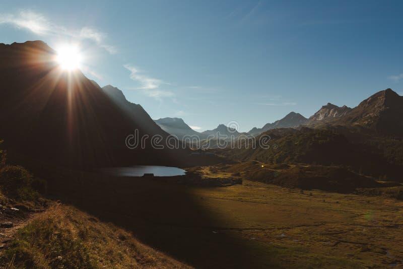 Nascer do sol cênico no piora val cercado pela escala de montanhas em um dia ensolarado Cumes su??os, Ticino fotografia de stock