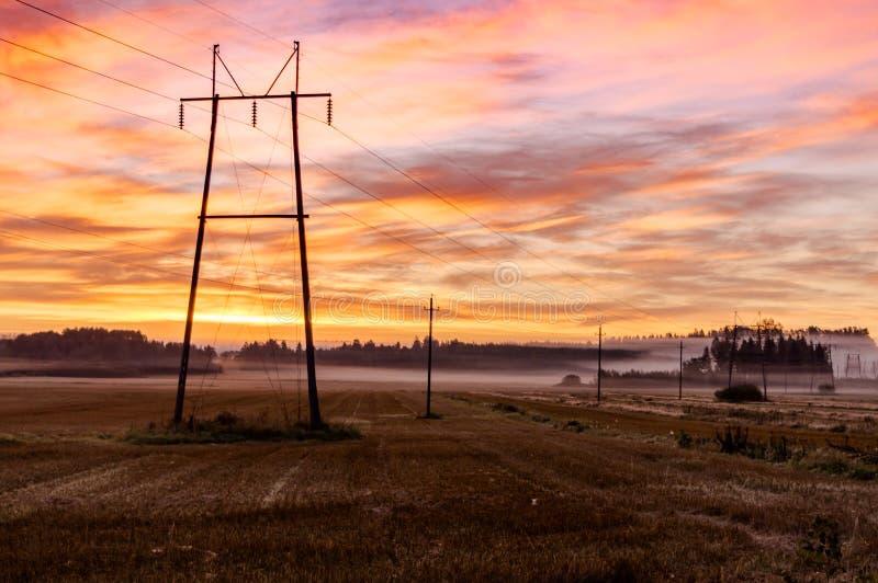 Nascer do sol, campo e linhas elétricas do outono foto de stock