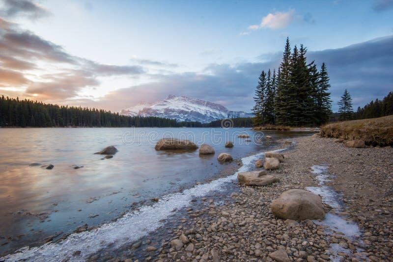 Nascer do sol colorido maravilhoso acima do lago da montanha da manhã com a ilha pequena da árvore e parte traseira alta do pico  imagens de stock royalty free
