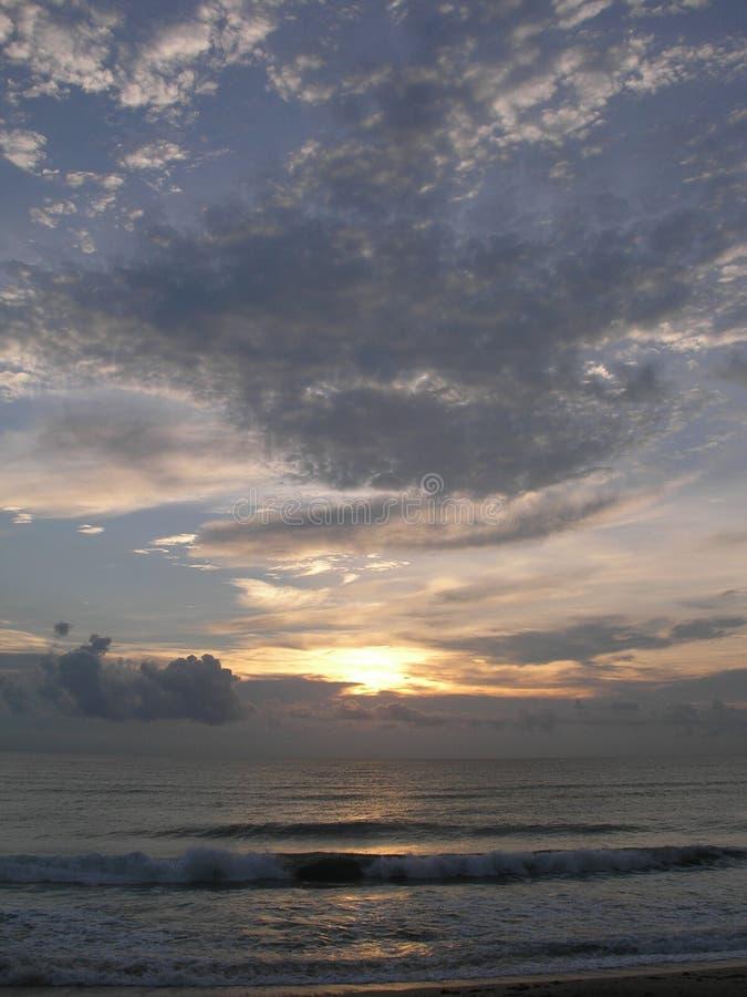 Nascer do sol com as nuvens de roda do oceano foto de stock