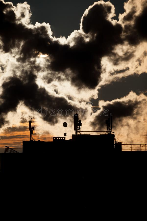Nascer do sol com silhuetas de uma antena de uma comunicação com antenas parabólicas no telhado de um arranha-céus fotos de stock royalty free